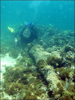 In this May 2003 photo, a diver measures a lombard cannon adjacent to a ballast pile, off the North coast of Haiti, at a site explorer Barry Clifford says could be the wreckage of Cristpher Colombus' flagship vessel the Santa Maria.
