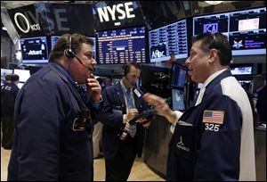 Traders John Santiago, left, and William McInerney, right, work on the floor of the New York Stock Exchange.