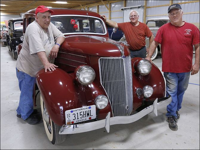 n4auction From left, Emery Ward III, John Ward, and Jeff Ward prepare to sell off their father's 1936 Ford cars at an auction in Sandusky on Saturday.