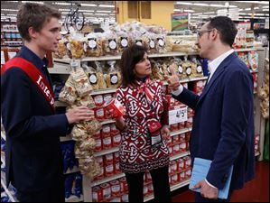 Interpreter Marco Celli, left, stands by as Tracy Sallah, forum co-coordinator, shows Massimo Caffagni products.