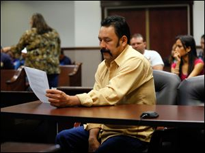 Herminio Morales reads paperwork before pleading guilty.