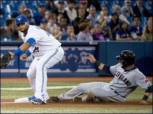 Blue Jays third baseman Juan Francisco, left, forces out Cleveland Indians' Yan Comes, right, at third base.
