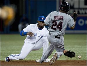 Blue Jays shortstop Jose Reyes, left, misses the catch on a throwing error by first baseman Adam Lind as Cleveland Indians' Michael Bourn is safe at second base.