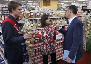 Interpreter Marco Celli, left, stands by as Tracy Sallah, forum co-coordinator, shows Massimo Caffagni products during an Italian Business Forum tour at The Andersons in Maumee.