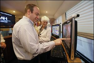Keith Meyer, left, does a quiz while fellow Kiwanian Pat Lora watches  during a tour of the  C-SPAN bus.