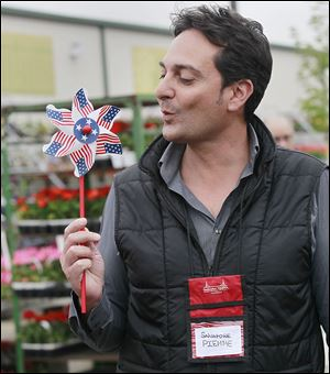 Salvatore Piemme blows an American-themed pinwheel toy  during an Italian Business Forum tour at The Andersons general store in Maumee.