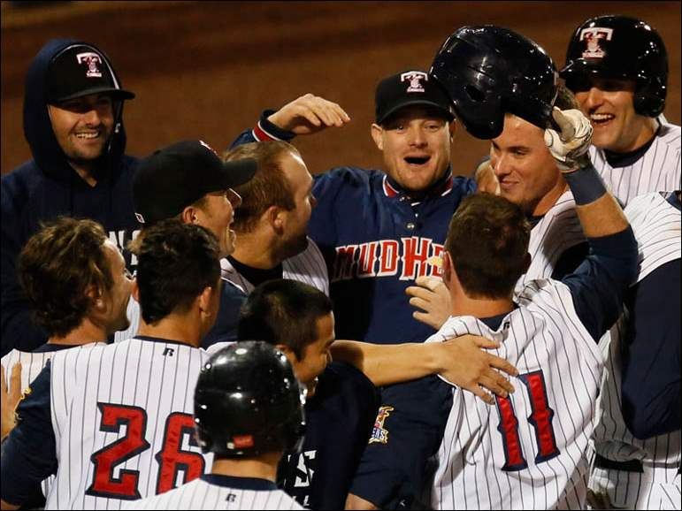 Toledo Mud Hens players surround Brandon Douglas after defeating Syracuse in the bottom of the ninth inning.