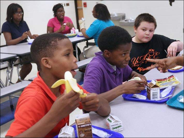 Shawn Carr, 12, left, Maurice Bates, 12, center, and Chris Conley, 11, right, eat lunch together.