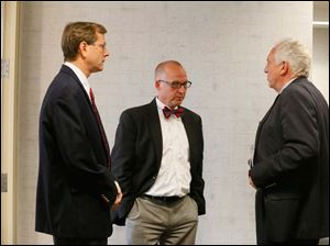 Transparency committee chairman Scott Borgemenke, center, meets with Lucas County Board of Elections member Jon Stainbrook, left, and board chairman Ron Rothenbuhler, right, in hallway before the start of the afternoon meeting.