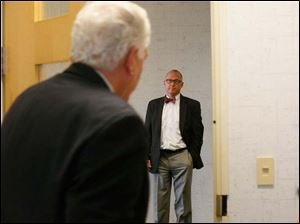 Transparency committee chairman Scott Borgemenke, right, awaits Lucas County Board of Elections member board chairman Ron Rothenbuhler, left, in hallway before the start of the afternoon meeting.