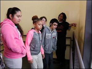 Fifth graders from Jones Elementary School Selina Boris, left, Azaya Pope, Neena Garcia, and Adam Buenavista, look out the window to see part of the school's playground pointed out to them by Young Men of Excellence member Devan Law, an eighth grader, right.
