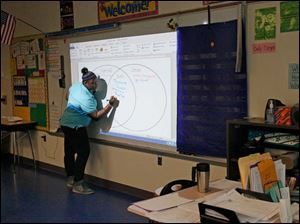 Daija Butler, a seventh grader and a member of Marshall Elementary School's Young Women of Excellence, helps visiting fourth graders from Jones and fourth graders teacher Karen Young's class talk about the special activities and attributes of each of their schools.