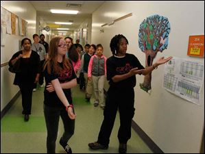 Brittney Sawyer, left, an eighth grader and member of Marshall Elementary School's Young Women of Excellence, left, and Devan Law, also an eighth grader and a member of Marshall Elementary School's Young Men of Excellence, are the tour guides for the visitors from Jones Elementary.
