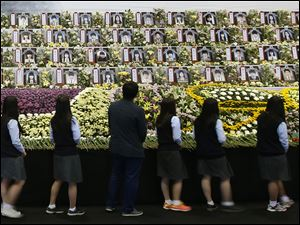 Middle school students view portraits of the victims of the sunken ferry Sewol at a group memorial altar in Ansan, South Korea, today.