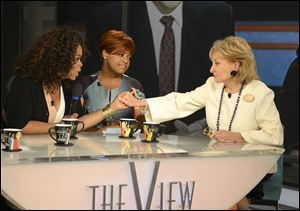 Oprah Winfrey, left, grasps hands with Barbara Walters, right, as co-host Sherri Shepherd looks on during a taping of Walters' final co-host appearance on 'The View.'