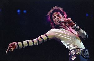 Michael Jackson leans, points and sings, dances and struts during the opening performance of his 13-city U.S. tour in this 1988 file photo