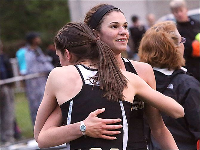 0008010100000000000 Perrysburg's Courtney Clody gets a hug after winning the 1600 in a meet-record 5:04.09. She also won the 800.