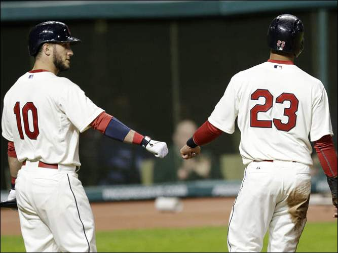 Cleveland Indians' Yan Gomes (10) congratulates Michael Brantley (23) after Brantley scored on a sacrifice fly.
