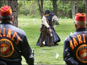 South Toledo resident and Civil War re-enactor Joseph Dowd, 15, center left, escorts his mother, Kathy Dowd, as she places flowers on the graves of veterans Saturday during the seventh annual Veteran's Memorial Program in South Toledo.  SEE PHOTO GALLERY at toledoblade.com