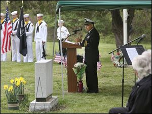Lt. Cmdr. Vidal Valentin addresses guests during the Veteran's Memorial program on Saturday in the former Toledo State Hospital Cemetery behind Bowsher High School.