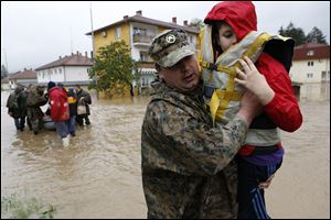A member of the Bosnian army carries a boy rescued from his home, during floods,   in the Bosnian town of Maglaj, 150 kms north of Sarajevo.