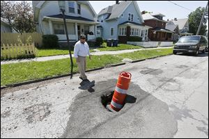 City Councilman Mike Craig points out a sink hole in the 700 block of Leonard Street near Prentice Park. Mr. Craig wants significantly more money for street repair for his council District 2.