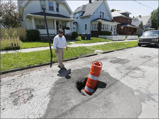 n3streets City Councilman Mike Craig points out a sink hole in the 700 block of Leonard Street near Prentice Park. Mr. Craig wants significantly more money for street repair for his council District 2.