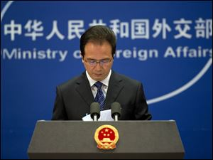 Foreign ministry spokesman Hong Lei looks at the papers before he speaks during a daily briefing at the Ministry of Foreign Affairs office in Beijing, China, today.