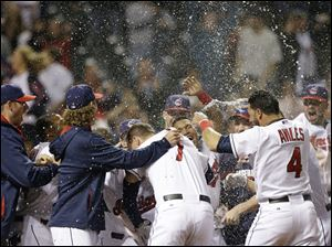The Cleveland Indians celebrate after Michael Brantley hit a game-winning solo home run off Detroit Tigers relief pitcher Al Alburquerque in the tenth inning.
