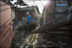 Relatives of Yekaterina Len, 61, try to clean debris in her destroyed house following a shelling in Slovyansk, eastern Ukraine, today. Slovyansk has been the major fighting ground between pro-Russian insurgents and Ukrainian government troops in eastern Ukraine.