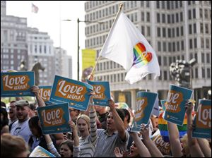 People hold up signs and cheer during a rally at City Hall, Tuesday in Philadelphia. Pennsylvania's ban on gay marriage was overturned by a federal judge Tuesday.