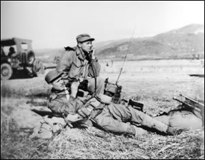 Cpl. Harold W. Reed, foreground with binoculars, is shown on the North Korean front. On the day he was killed, Chinese troops attacked in snowy, freezing weather.  Corporal Reed's family learned of his death the day after Christmas, 1950. His flag-draped coffin is to land today in Detroit and is to be buried in the family plot his mother had long hoped would be his final resting place.