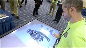 Michael Fieldson, the civilian project manager for the Tactical Assault Light Operator Suit at McDill Air Force Base, looks at sketches of the body armor exoskeleton during the Special Operations Forces Industry Conference in Tampa, Fla.
