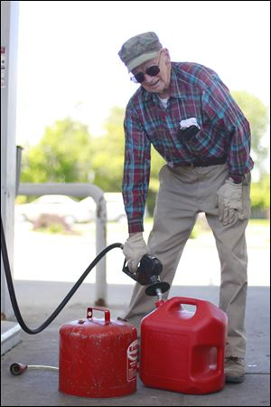 Ray Elieff fills up gas cans in preparation for how he will spend his Memorial Day weekend: cutting his grass.