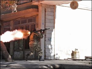 An Afghanistan's National Army (ANA) soldier fires his weapon at the site of a clash between insurgents and security forces over Indian Consulate in Herat, Afghanistan today.