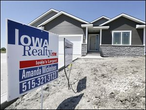 A sign sits in front of a new home for sale in West Des Moines, Iowa.