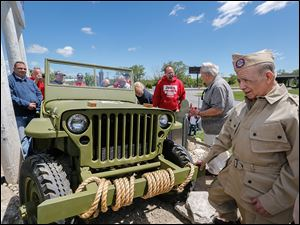 World War II veteran and Jeep retiree Lupe Flores, right, checks out the restored Jeep at Chrysler's Toledo Assembly Complex last month.