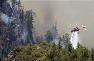 A firefighting helicopter drops water on a forest fire in Oak Creak Canyon in Sedona, Ariz., Thursday. The human-caused Slide Fire started Tuesday and had burned 7 1/2 square miles in and around Oak Creek Canyon, a scenic recreation area along a highway between Sedona and Flagstaff that normally would be teeming with tourists as the Memorial Day weekend approaches.