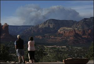Tourists watch the Slide Fire from a scenic overlook as it burns up Oak Creek Canyon nearby on Thursday in Sedona, Ariz.