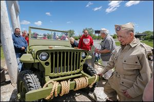 World War II veteran and Jeep retiree Lupe Flores, right, looks at the restored Jeep. Behind him is Ron Szymanski, and Bob Kiss, one of the painters on the project.