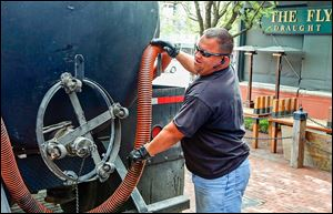 Clay Carrillo-Miranda pumps used grease into a tanker in Fort Worth. To thwart thieves, he stakes out the restaurants that contract with his employer, Haltom City's Best Grease Service, because, he says, thieves can strike fast.