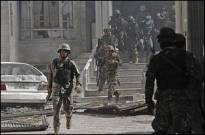 Afghanistan's National Army soldiers walk at the site of a clash between insurgents and security forces at the Indian Consulate in Herat, Afghanistan. Gunmen armed with machine guns and rocket-propelled grenades attacked the Indian Consulate.