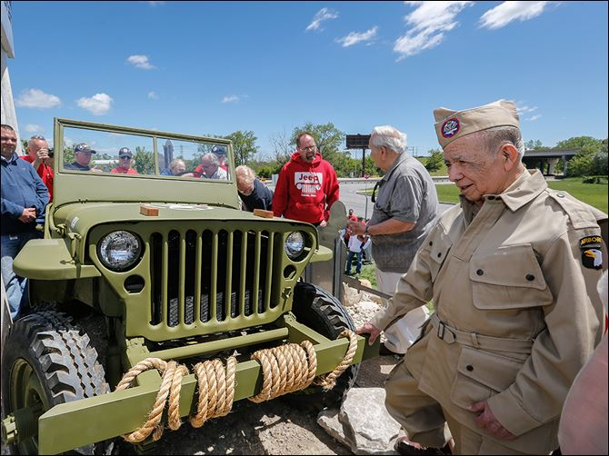 n7willys-3 World War II veteran and Jeep retiree Lupe Flores, right, looks at the restored Jeep. Behind him is Ron Szymanski, and Bob Kiss, one of the painters on the project.
