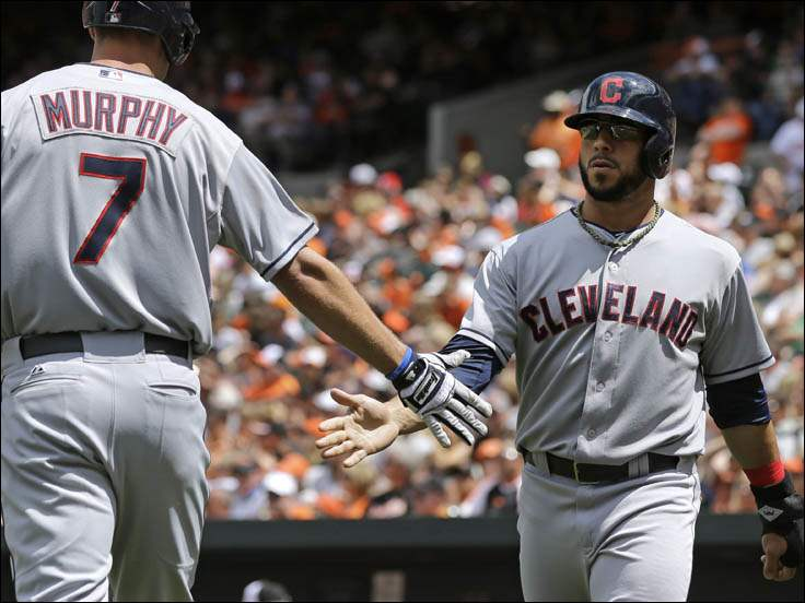 Cleveland Indians second baseman Mike Aviles, right, congratulates teammate David Murphy after scoring on a groundout by Ryan Raburn.