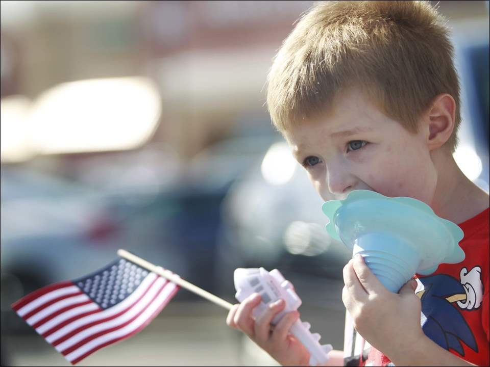 Skyler Jeko, 3, enjoys a snow cone during an event that showcases a variety of police and rescue agencies held in the parking lot of the Wal-Mart in Perrysburg.