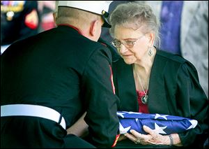 Dorothy Sobczak, Cpl. Harold Reed's wife at the time of his death in 1950, is presented with a folded American flag at Mr. Reed's funeral service at Ottawa Hills Memorial Park in Toledo on Saturday.