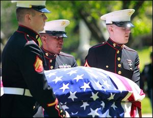 Marines Cpl. Kenneth Arp, left, Sgt. Marshall Grayson, center, and PFC. Austin Adams, right, carry the flag-covered casket of Cpl. Harold W. Reed to his final resting place.
