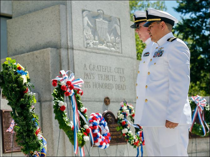 25n1vidal Navy CWO 4 Michael Joseph, left, and Navy Lt. Cmdr. Vidal Valentin stand at attention after placing the wreath during the annual Memorial Day service at the Civic Center Mall.