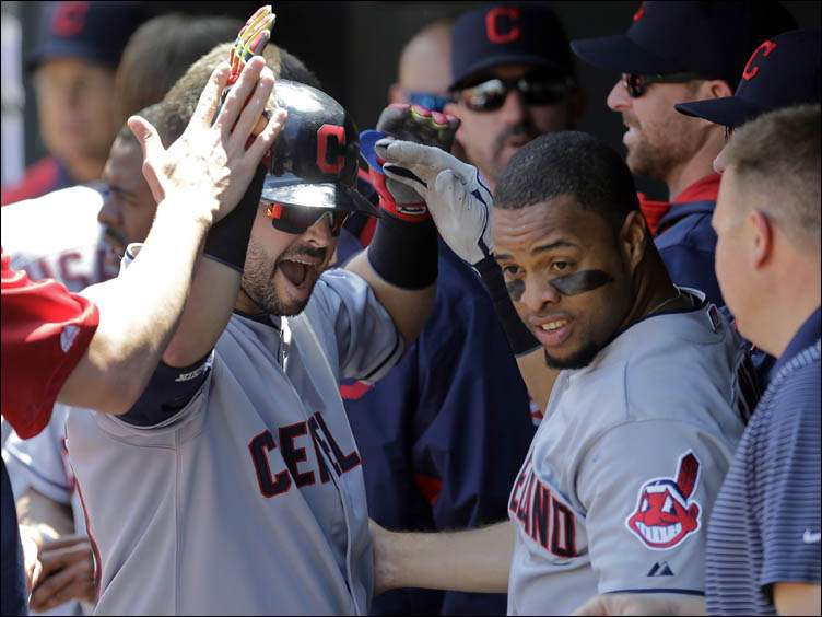 Cleveland Indians' Nick Swisher, left, and Carlos Santana high-five teammates in the dugout after Santana scored on Swisher's sacrifice fly.