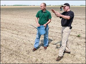 Eric Richer, Ohio State Extension educator, left, talks to Metamora farmer Keith Truckor on his 65 acres of corn crop, where he took nitrogen samples.